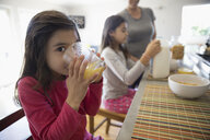 Portrait smiling girl drinking orange juice at breakfast bar in kitchen - HEROF26472