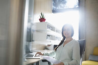 Portrait smiling businesswoman working at laptop in sunny office - HEROF26484