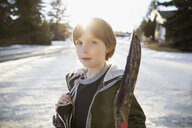 Portrait confident, serious boy holding ice hockey stick and ice skates on sunny, snowy road - HEROF26490