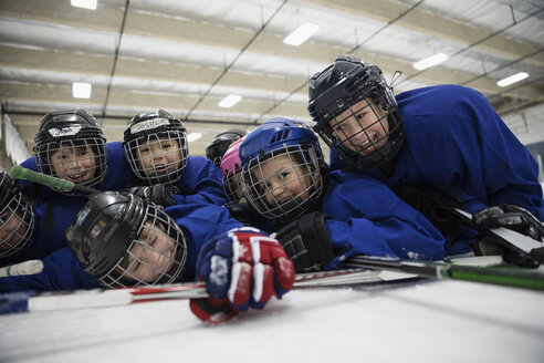 Portrait playful boy ice hockey players laying on ice hockey rink - HEROF26505