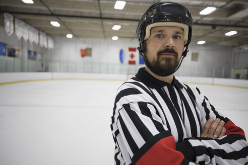 Portrait confident male ice hockey referee with arms crossed on ice hockey rink - HEROF26511