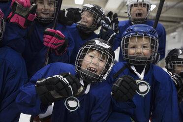 Portrait enthusiastic boy and girl ice hockey players celebrating - HEROF26514