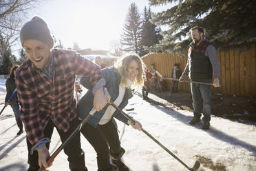 Playful couple playing ice hockey in sunny, snowy driveway - HEROF26517