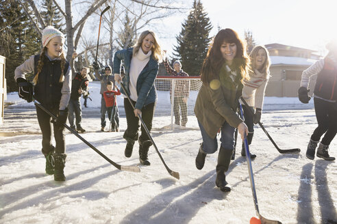 Playful mothers and daughters playing ice hockey in sunny, snowy driveway - HEROF26520