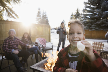 Portrait enthusiastic boy roasting marshmallows at fire pit with family in snowy driveway - HEROF26523
