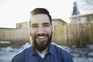 Portrait enthusiastic, smiling young brunette man with beard on sunny road - HEROF26544