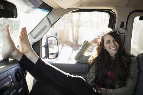 Portrait confident barefoot brunette woman with feet up on dashboard in van - HEROF26553