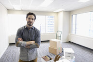 Portrait confident businessman with cardboard boxes in new office - HEROF26574