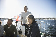 Portrait senior woman on sunny sailboat with friends - HEROF26643