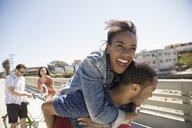 Playful couple piggybacking on sunny sidewalk - HEROF26664