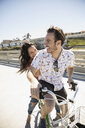 Playful couple laughing on bicycle on sunny sidewalk - HEROF26667