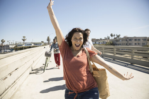 Portrait enthusiastic, playful woman running on sunny California bridge - HEROF26670