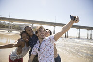 Playful friends with camera phone taking selfie on sunny beach - HEROF26673