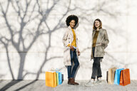 Portrait of two happy women with shopping bags standing at a wall - JRFF02763