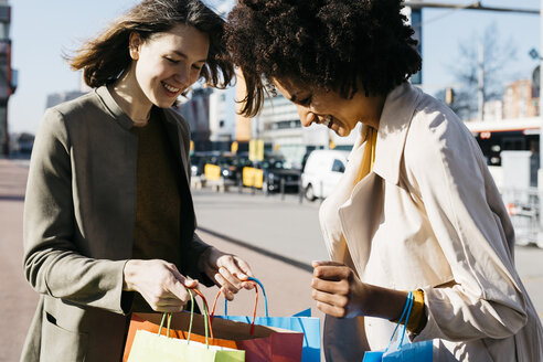 Two happy women with shopping bags in the city checking the purchase - JRFF02772