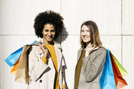 Portrait of two happy women with shopping bags standing at a wall - JRFF02778