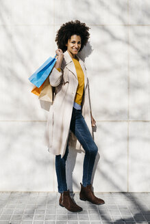 Portrait of smiling woman with shopping bags standing at a wall - JRFF02781