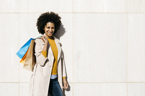 Portrait of smiling woman with shopping bags standing at a wall - JRFF02784