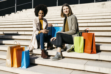 Portrait of two happy women with shopping bags sitting on stairs - JRFF02790