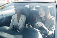 Two women driving in a car through the city - JRFF02799