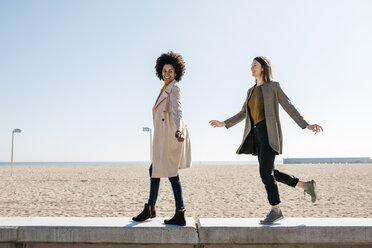 Two happy friends walking on the promenade enjoying leisure time - JRFF02808