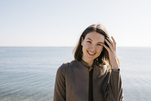 Portrait of smiling woman with the sea in background - JRFF02814