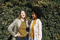 Portrait of two happy women in front of a hedge - JRFF02817