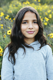 Close-up portrait of smiling girl standing amidst plants during sunset - CAVF62088