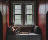 Side view of shirtless cute boy sitting on alcove window seat at home - CAVF62145