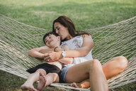 High angle view of mother kissing son while relaxing on hammock in forest - CAVF62148