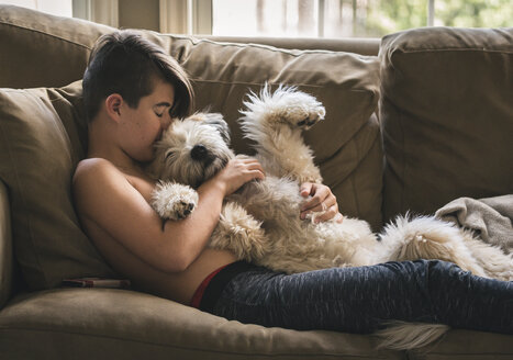 Side view of shirtless boy with dog relaxing on sofa at home - CAVF62151