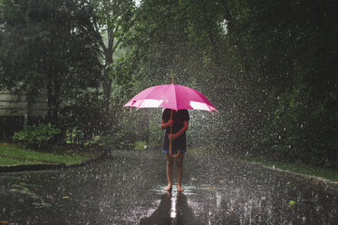 Girl carrying umbrella while standing on road against trees during rainfall - CAVF62163