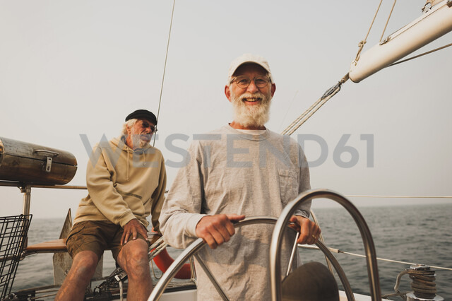 Portrait of senior man with friend sailing boat on sea against clear sky - CAVF62181