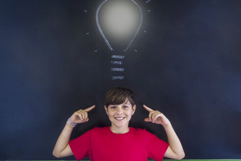 Portrait of smiling schoolboy with light bulb drawing on blackboard standing in classroom - CAVF62205