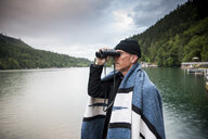 Side view of man looking through binoculars while standing by lake against cloudy sky in Olympic National Park - CAVF62217