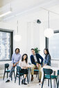 Portrait of smiling business people sitting in creative office - CAVF62280