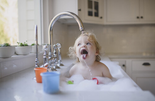 Cute shirtless girl drinking water from faucet while bathing in sink at home - CAVF62283
