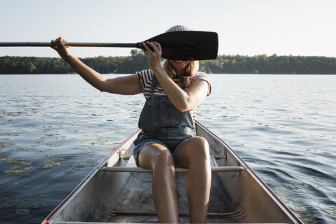 Happy woman hiding face with oar while sitting in boat on lake against sky at Algonquin Provincial Park - CAVF62292