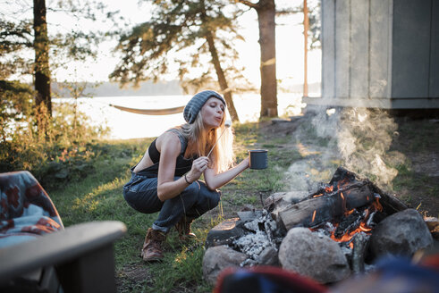 Woman cooking marshmallow while crouching by campfire in forest - CAVF62301