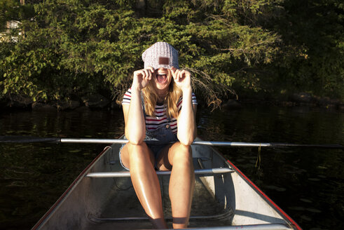 Happy woman covering face with knit hat while sitting in boat on river against trees at Algonquin Provincial Park - CAVF62304