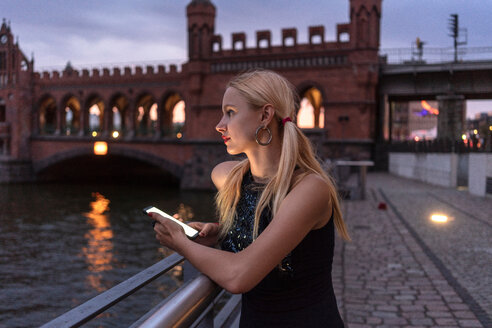 Hipster woman by riverside, Berlin, Germany - CUF49299