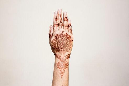 Hand with henna tattoo making gesture - CUF49356