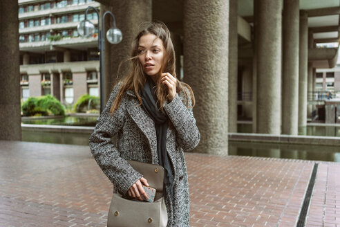 Young woman on walkway of office building, London, UK - CUF49362