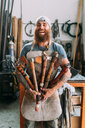 Axe maker showing off variety of handcrafted axes - CUF49395