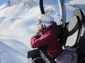 Young woman skier wearing helmet and ski goggles looking out from ski lift,  Alpe Ciamporino, Piemonte, Italy - CUF49413