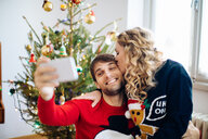 Couple taking selfie in front of Christmas tree at home - CUF49425