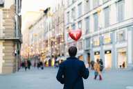 Man with heart shaped balloon at piazza, Firenze, Toscana, Italy - CUF49440
