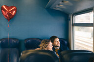 Couple with heart shaped balloon looking out window of train - CUF49446