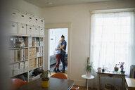 Affectionate couple hugging in apartment doorway - HEROF26706