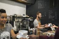 Baristas serving customers in coffee shop - HEROF26721